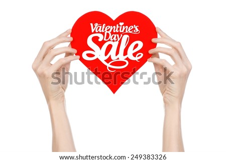 Valentine's Day and sale topic: Hand holding a card in the form of a red heart with the word Sale isolated on white background in studio - stock photo