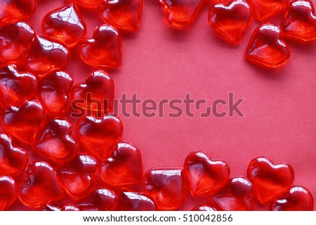 valentine's day background, many red transparent hearts lying on pink sheet of paper