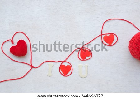 "Valentine's Day background: red knitting thread,bobbin,red wooden hearts and plush heart  on a white wooden surface. Message: ""I love u"". Free space for a text"
