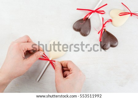 Valentine's Day background: white wooden table with candy in the form of hearts on a stick, girl bow festive red ribbons on one of it, top view, copy space