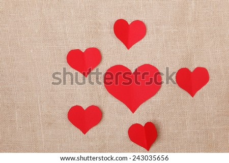 Valentine's Day background with red paper hearts on  burlap background - stock photo