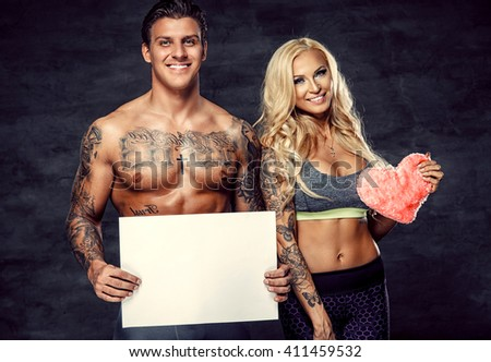 Valentine's day celebration. Shirtless muscular guy holding white sheet of paper (for your text). Smiling blond female handing pink heart.