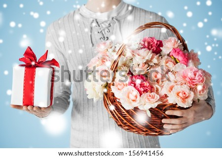 valentine's day, christmas, x-mas, winter, happiness concept - man holding basket full of flowers and gift box. - stock photo