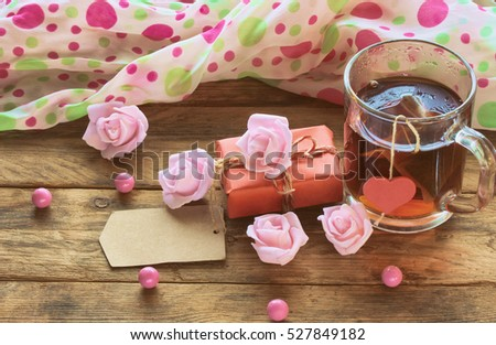 valentine's day composition, cup with tea bag, paper tag, pink roses, beads on wooden table, retro toned image