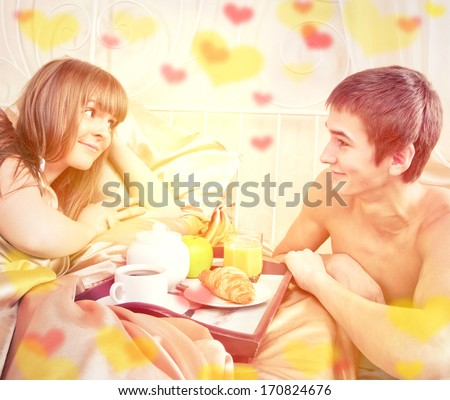 Valentine's day concept. Happy man and woman having luxury hotel breakfast in bed together  - stock photo