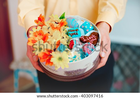 Valentine's Day concept shot: Male hands holding gift box filled with flowers and fruit candy covered by blue and milk chocolate; shot in shallow depth of field