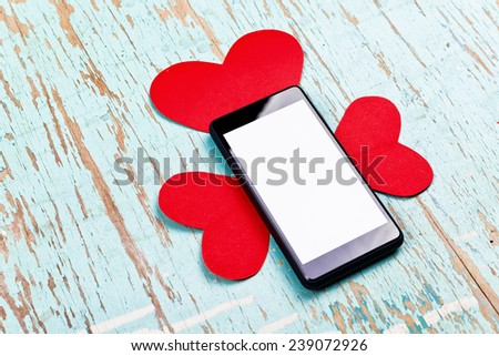 Valentine's Day copy space on smart phone with blank screen and red paper hearts on old grunge wood texture. - stock photo