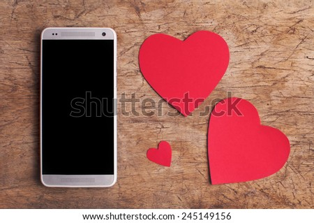 Valentine's Day copy space on smart phone with blank screen and red paper hearts on old wooden table  - stock photo