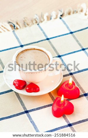 Valentine's day cup of coffee with pair of heart shaped sweet chocolates and candles. Celebration surprise. - stock photo