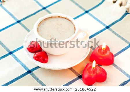 Valentine's day cup of coffee with red heart shaped sweet chocolates and pair of candles. Celebration surprise. - stock photo