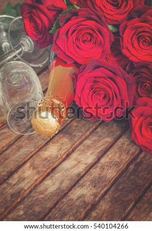 Valentine's day dark red roses and neck of champagne wine, retro toned