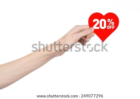 Valentine's Day discounts topic: Hand holding a card in the form of a red heart with a discount of 20% on an isolated white background in studio - stock photo