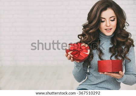 Valentine's Day - dreaming cute woman. Beautiful woman open red gift box heart. - stock photo