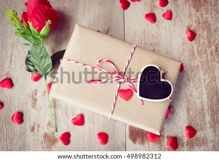 Valentine's Day, Gift box of kraft paper with a red and white rope,red rose,heart black board, on wood background