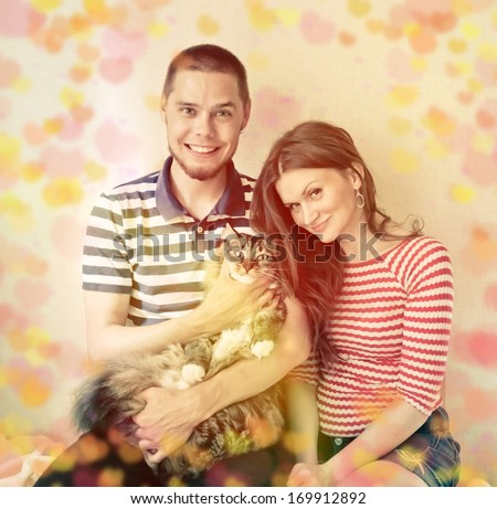 Valentine's Day, happy young couple at home with their cat  - stock photo