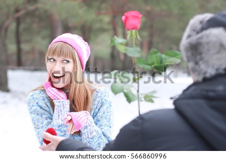 Valentine's Day in the winter forest, guy gives his girlfriend  rose, Declaration of love in winter park, Gift of the day of lovers,  marriage proposal