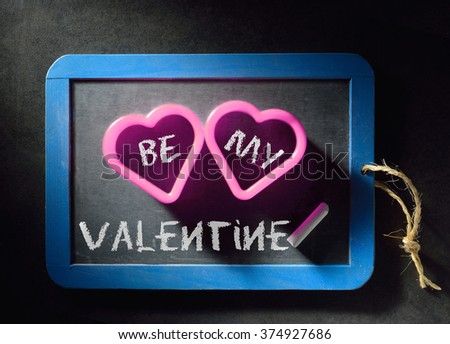Valentine's day invitation to be my Valentine. White chalk letters on blackboard background and two pink hearts. - stock photo
