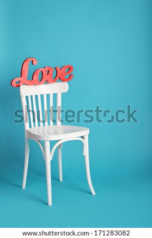 Valentine's Day. Place for love freely. The word love red. Love inscription on a blue background beautiful. The word love on a chair in white. Love Story. Text about love. Space for text. - stock photo