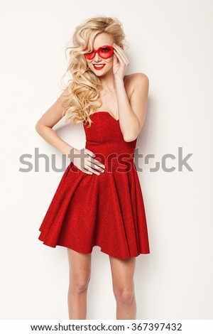 valentine's day portrait of an attractive young blonde girl with heart shaped glasses in red dress - stock photo