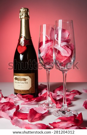 Valentine's Day still life with a bottle of champagne and a pair of flute glasses. - stock photo