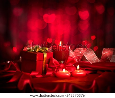 Valentine's Day. Valentine Red Heart shaped candles and Gift on Red Silk over glowing background. Beautiful Valentine card art design - stock photo