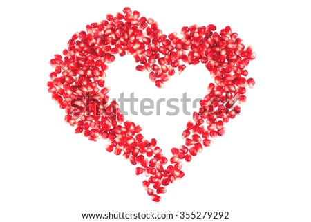 Valentine's heart shape made by pomegranate seeds (isolated on white) - stock photo