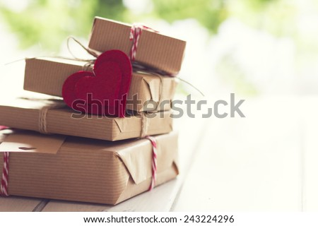 Valentine. Some paper parcels wrapped tied with a tag. A red heart on a gift box wrapped with paper kraft and tied with red & white baker's twine on a white wooden table. Vintage Style. - stock photo