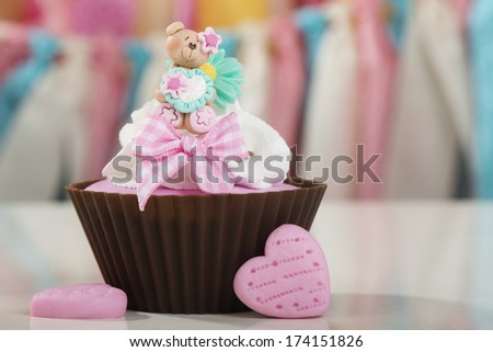 Valentine teddy bear cupcake with pink hearts and bow - stock photo