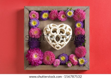 Valentine vintage heart in decorative frame surrounded by flowers - stock photo