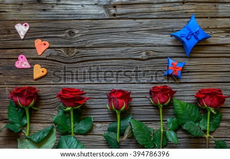 Valentines background with red roses arranged as a border on a rustic wooden table, hearts and gifts for a sweetheart with copy space - stock photo