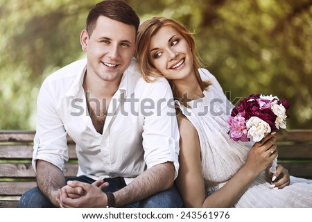 Valentines day and love concept.Beautiful couple happy together sitting in park and smiling. - stock photo