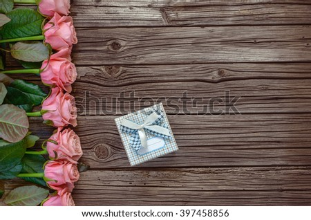 Valentines Day background bordered by roses row on side with little gift box and copy space over weathered wood - stock photo