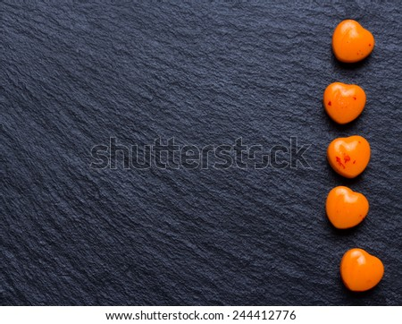 Valentines day background. Orange heart shaped pills or candy on grunge black slate background. Copy space. - stock photo