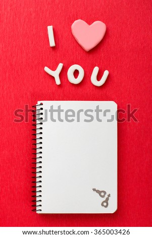 Valentines day background with copy space. Open notebook with the written word Love you on red background. Top view - stock photo