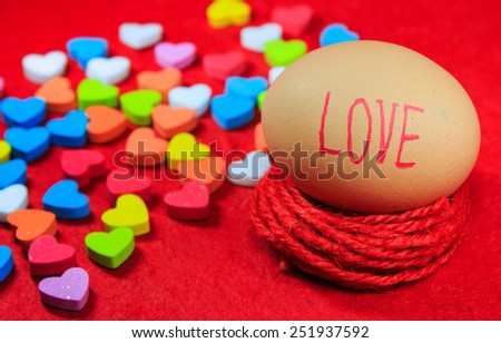 Valentines day background with love text on egg and colorful heart shaped on red paper. - stock photo