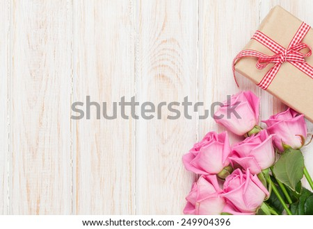 Valentines day background with pink roses and gift box over wooden table. Top view with copy space - stock photo