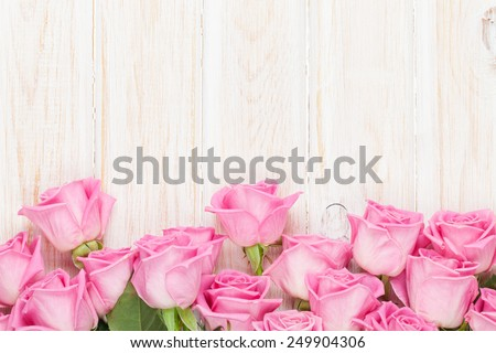 Valentines day background with pink roses over wooden table. Top view with copy space - stock photo