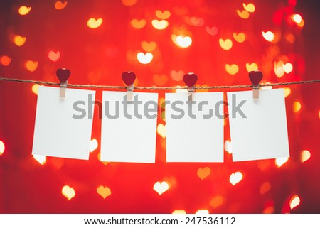 Valentines Day. Blank photo frames hanging on the heart clothesline . Isolated on heart bokeh background. Vintage style. - stock photo