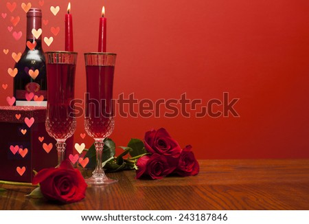 Valentines day: bottle of vine, glasses, red roses, candles, hearts and present  - stock photo