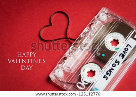 Valentines day card - audio cassette with magnetic tape in shape of heart on red background - stock photo