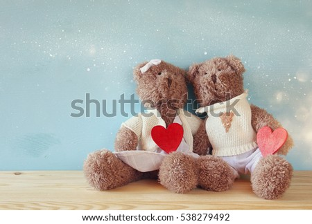 Valentines day concept. Couple of cute teddy bears holding hearts, sitting on wooden table. Glitter overlay