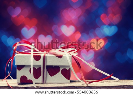 Valentines day concept with gift box over heart shaped bokeh