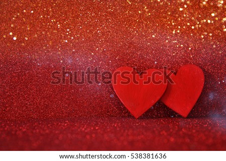 Valentines day concept. Wooden red hearts on red shiny background