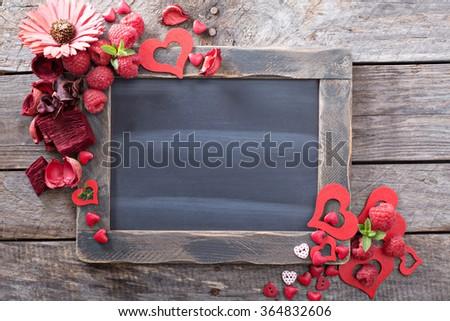 Valentines day decorations around a chalkboard copyspace - stock photo