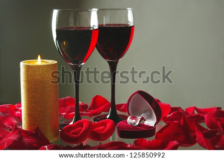 Valentines Day. Gift, two glasses of red wine, burning candle and two hearts