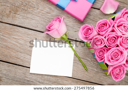 Valentines day greeting card or photo frame and gift box full of pink roses over wooden table. Top view - stock photo
