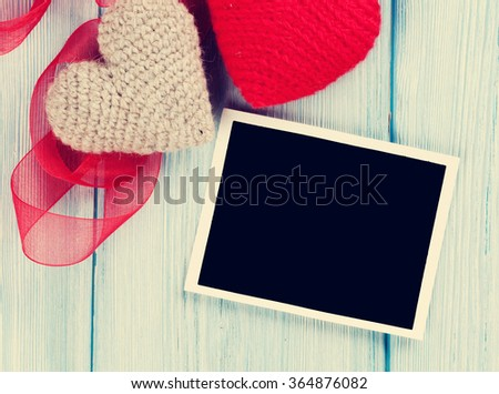 Valentines day greeting card or photo frame and handmaded hearts over blue wooden table. Top view with copy space. Retro toned - stock photo