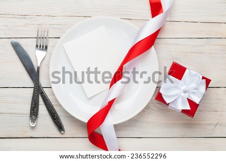 Valentines day greeting card over plate and gift box. On white wooden table - stock photo
