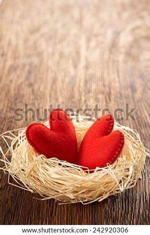 Valentines Day. Handmade Red Hearts Couple in nest made of straw. Love concept on wooden background - stock photo