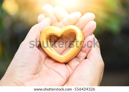 Valentines day Hands of person holding wood heart under the sunlight